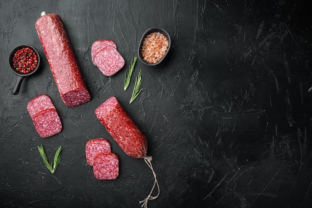 Plakjes salami met groenten set, op zwarte donkere stenen tafel, bovenaanzicht plat gelegd