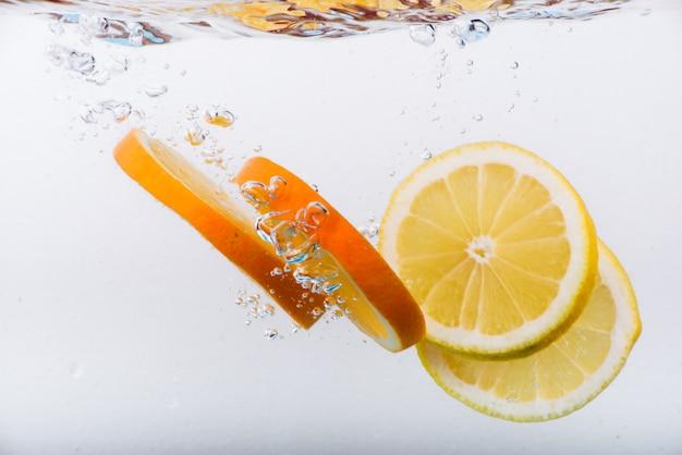 Plakjes sinaasappel en citroen in water met bubbels