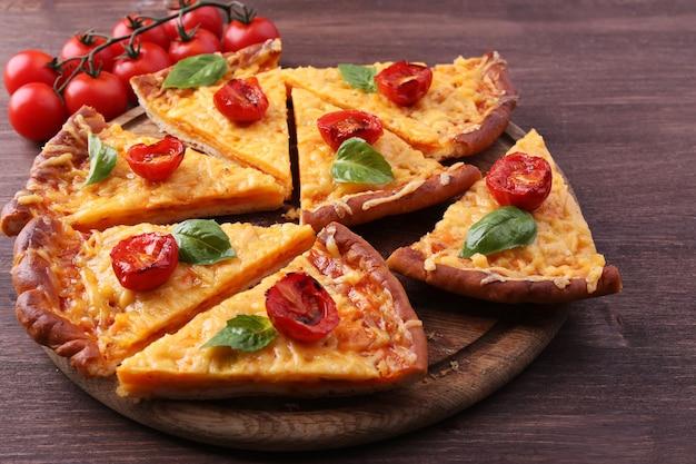 Plakjes smakelijke kaas pizza met basilicum en kerstomaatjes op tafel close-up
