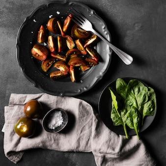 Plakjes tomaten met groenten en zout