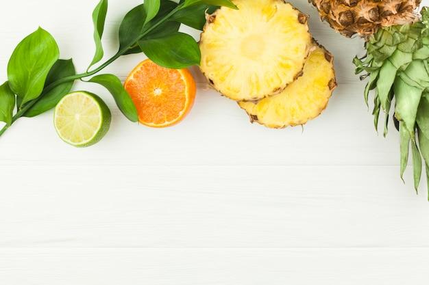 Plakjes tropisch fruit en groene bladeren