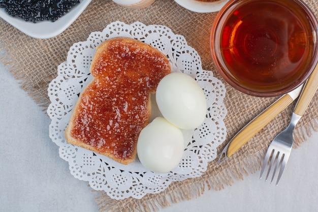 Plakjes vers wit brood met jam en gekookte eieren op marmeren achtergrond.