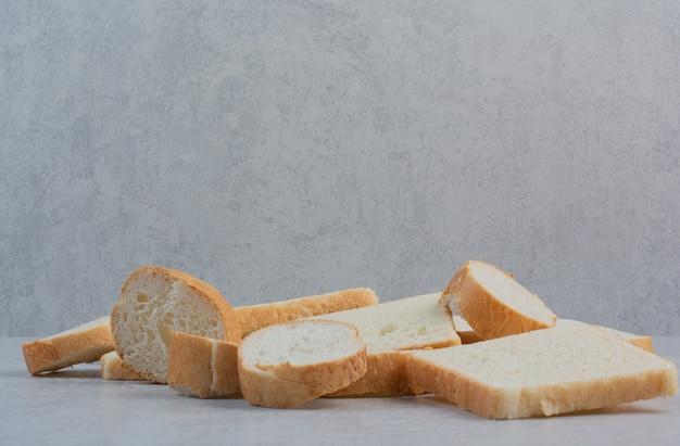 Plakjes vers wit brood op marmeren achtergrond.