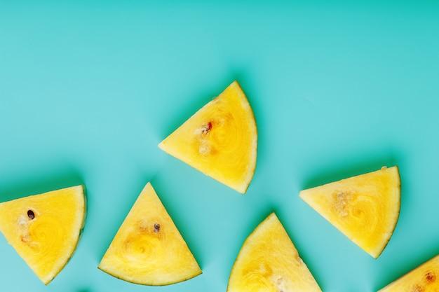 Plakjes verse gele watermeloen op blauw