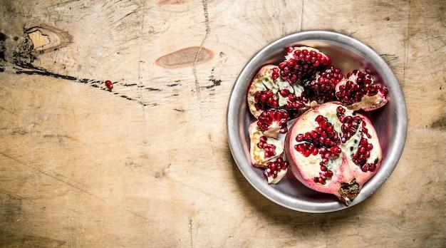 Plakjes verse granaatappel in een kom. op een houten tafel. vrije ruimte voor tekst. bovenaanzicht