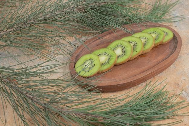 Plakjes verse kiwi op houten plaat.