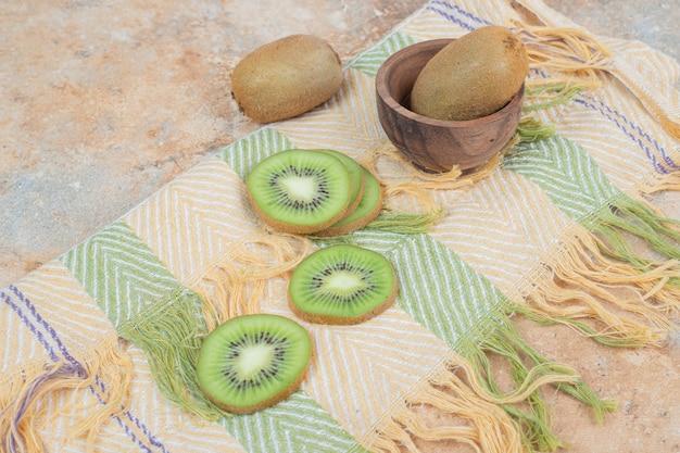 Plakjes verse kiwi op kleurrijk tafellaken.