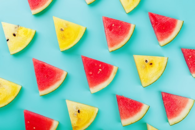 Plakjes verse plakjes gele en rode watermeloen op blauw.