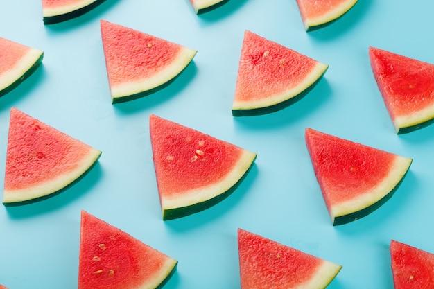 Plakjes verse plakjes rode en gele watermeloen op blauw.