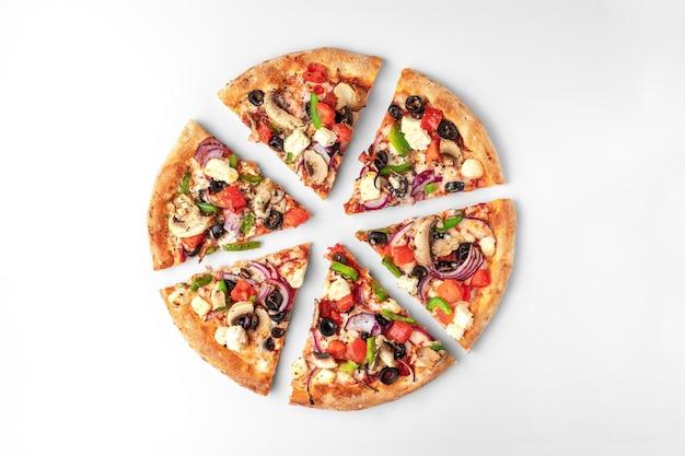 Plakjes verse ronde pizza met kippenvlees, groenten, champignons en kaas bovenaanzicht op een wit en grijs oppervlak. natuurlijke schaduw met kopie ruimte