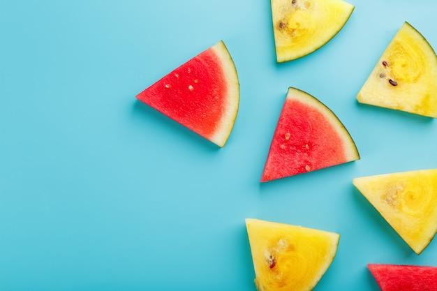 Plakjes verse stukjes gele en rode watermeloen op blauw.