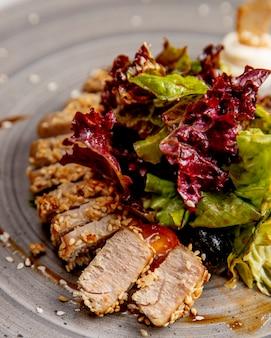 Plakjes vlees geserveerd met sesamzaadjes van sla en saus