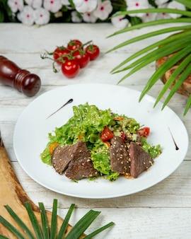 Plakjes vlees met groenten gegarneerd met sesam