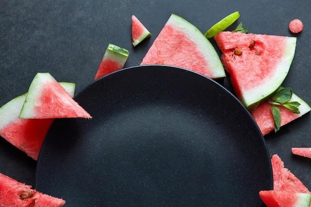 Plakjes watermeloen geplaatst in een cirkel van zwarte plaat. ruimte voor tekst