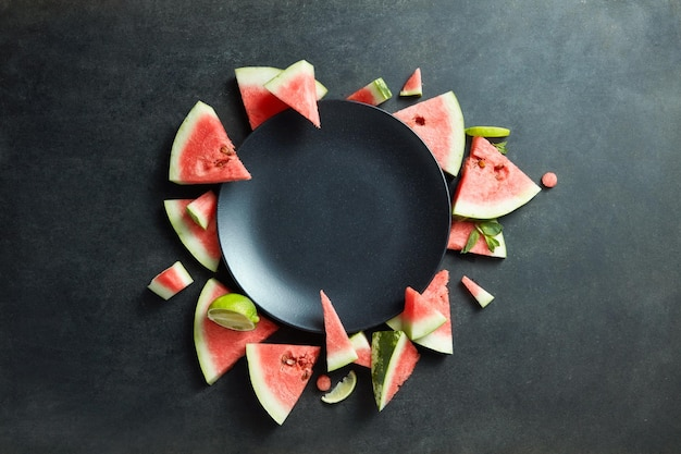 Plakjes watermeloen geplaatst in een cirkel van zwarte plaat