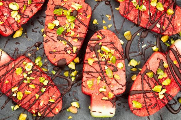Plakjes watermeloen in ijs of popsical vorm met chocolade en pistachenootjes decoratie, bovenaanzicht