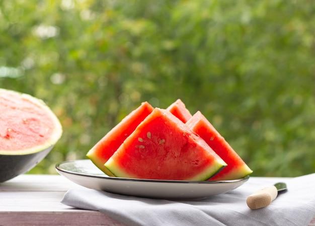 Plakjes watermeloen op een bord, een halve watermeloen op de achtergrond, buiten. gezond eten.