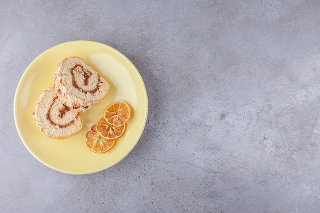 Plakjes zoete roomrol op een bord met gedroogde citroen.
