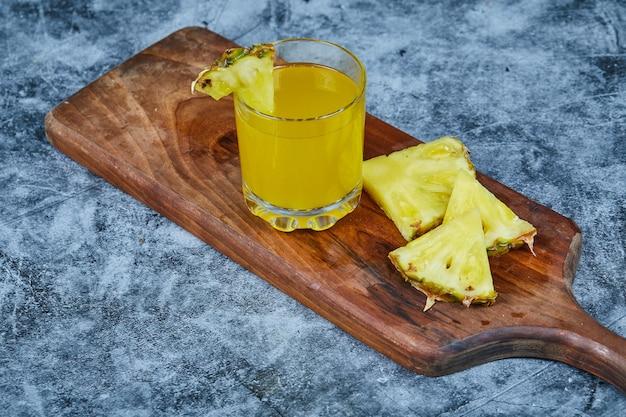 Plakken ananas en ananassap op houten plank