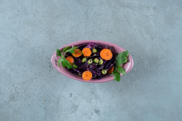 Plakken van diverse groente en greens in roze kom.