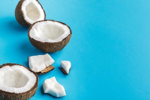 Plakken van gebroken tropische kokosnoten op blauw. bovenaanzicht