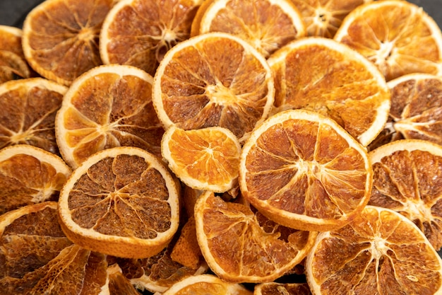 Plakken van gedehydrateerde sinaasappel op zwarte steen. selectieve aandacht.