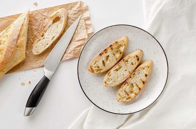 Plakken van geroosterd frans stokbrood op witte plaat voor ontbijt