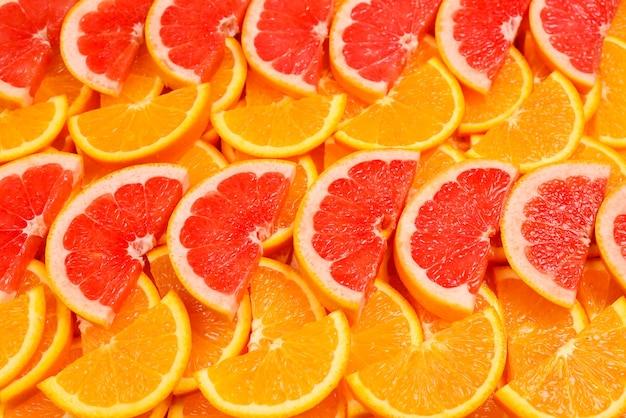 Plakken van sinaasappelen en grapefruits als achtergrond.