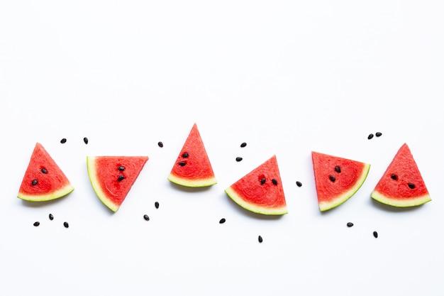 Plakken van watermeloen met zaden op wit worden geïsoleerd dat