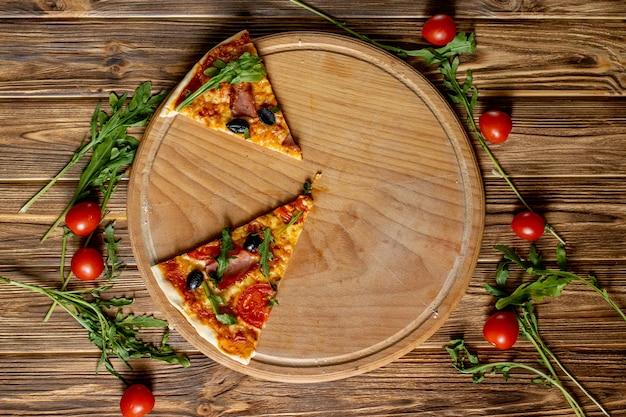 Plakkenpizza op houten raad, met tomaten en basilicum, italiaanse stijl op oude houten lijst, hoogste mening.