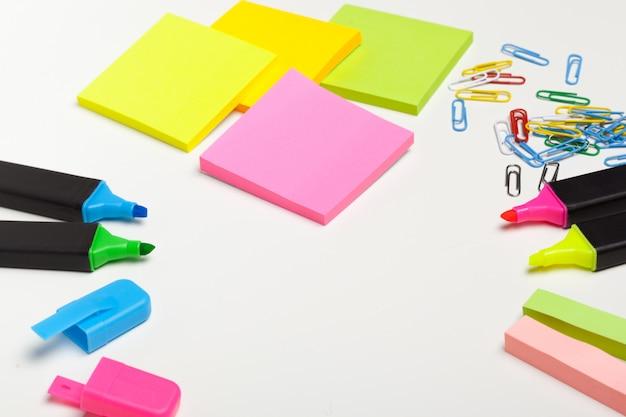 Plaknotities met stiften, gekleurde pennen, paperclips die op een tafel liggen
