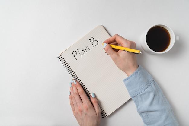 Plan b geschreven op laptop op witte achtergrond. vrouwelijke handen en kladblok in de buurt van kopje koffie