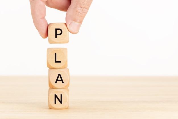 Plan concept. hand met een houten blok met tekst op tafel.