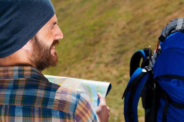 Plan de beste manier om er te komen. close-up van een jonge man die in de buurt van een rugzak zit en een kaart vasthoudt en glimlacht