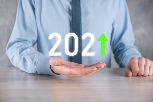 Plan een positieve bedrijfsgroei in het concept van het jaar 2021. zakenmanplan en verhoging van positieve indicatoren in zijn bedrijf, bedrijfsconcepten opgroeien.