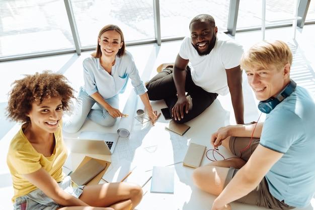 Plan gemeenschappelijk werk. bovenaanzicht van positieve slimme internationale studenten die op de grond zitten en samen werken terwijl ze studeren