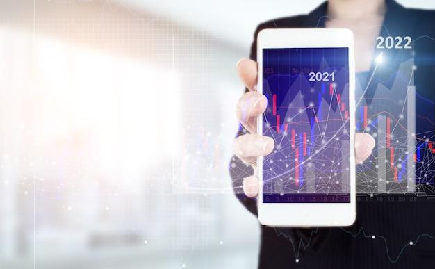 Plan groei en toename van positieve indicatoren in zijn bedrijf. hand houden witte smartphone met digitale hologram groei grafiek grafiek teken op lichte onscherpe achtergrond. welkom jaar 2022.