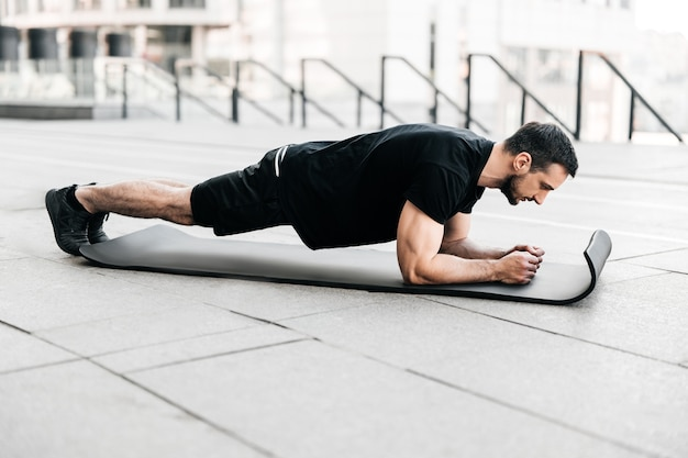 Plan het! opleiding in het concept van de grote stad. sportieve jongeman die zwarte sportkleding draagt en plankpositie doet tijdens het sporten op asfaltwegen. moeilijke oefening. zelfzorgconcept.