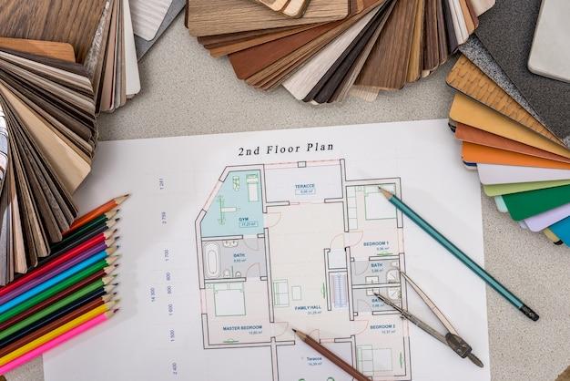 Plan huis met houten modellen, potloden, pen op tafel.