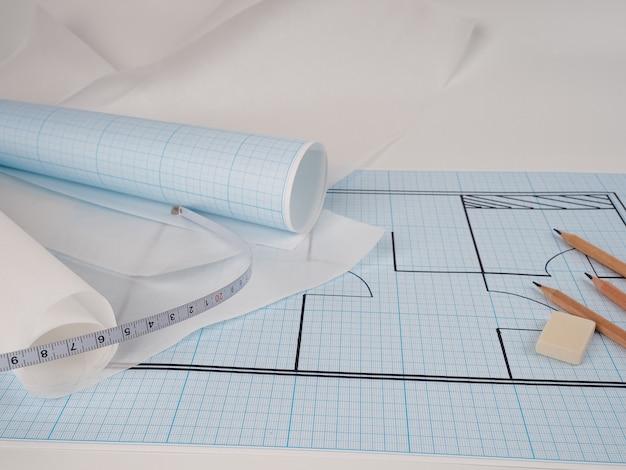Plan op ruitjespapier, het proces van planbouw en nieuw ontwerp van gezellig huis, pachuca nieuw appartement. ruitjespapier voor schetsen, potloden en ruitjespapier op rol