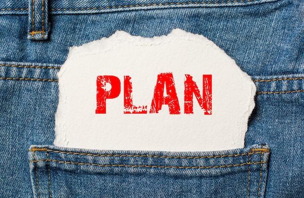 Plan op wit papier in de zak van blauwe spijkerbroek