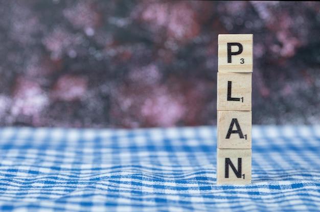 Plan schrijven met zwarte letters op houten dobbelstenen op een blauwe geruite handdoek. hoge kwaliteit foto