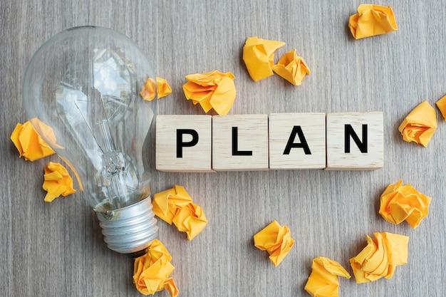Plan-tekst houten kubus en verkruimeld papier met gloeilamp