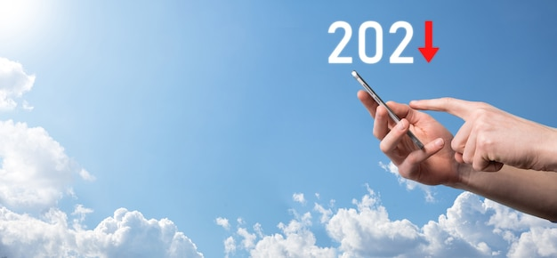 Plan zakelijke negatieve groei in het concept van het jaar 2021. zakenman plan en toename van negatieve indicatoren in zijn bedrijf, dalen naar beneden bedrijfsconcepten. handgreep op hemelachtergrond.