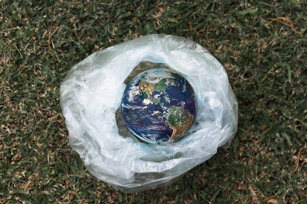 Planeet aarde in een plastic zak, opwarming van de aarde door broeikaseffect planeet aarde in een plastic zak. het concept van vervuiling door plastic puin