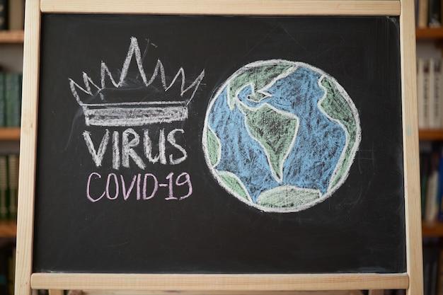 Planeet aarde in gevaar waarschuwing voor uitbraak. geschreven wit krijt op bord in verband met epidemie van coronavirus wereldwijd. covid 19 pandemische tekst op zwarte achtergrond