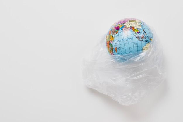 Planeet in plastic zak op grijze achtergrond