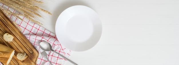Plank eettafel met witte plaat, bestek, servet en kopie ruimte