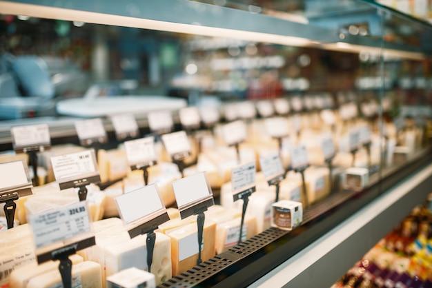 Plank met kaasplakken in voedselopslag, niemand. zuivelproducten sectie in supermarkt
