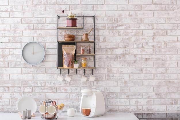 Plank met keukengerei op bakstenen muur